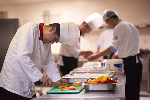 chef in hotel kitchen  slice  vegetables with knife and prepare food-1
